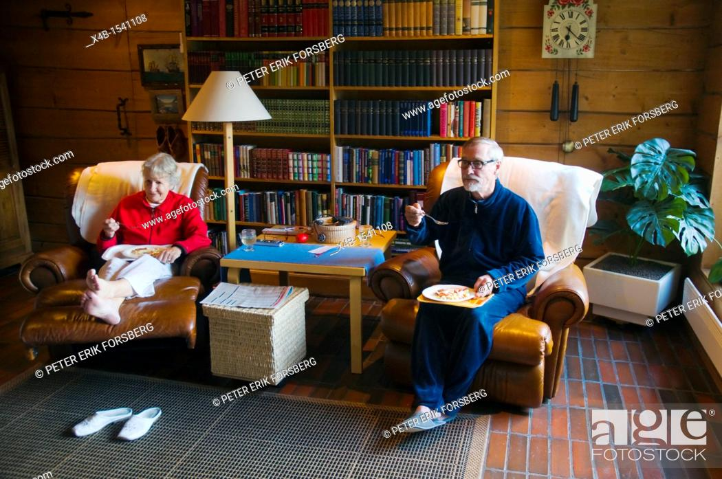 Stock Photo: Couple in their early 70s eating and watching television Finland Europe.