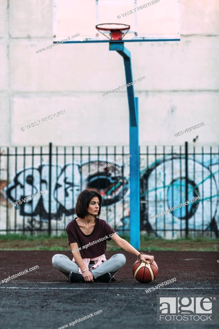 1575c21ebba8 Young woman sitting with basketball on outdoor court, Stock Photo ...