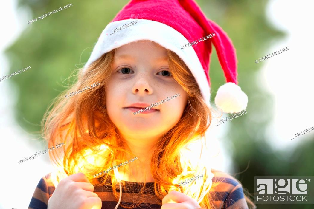 Stock Photo: A little girl dressed in a santa hat and fairy Christmas lights.