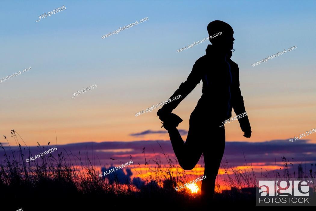 Stock Photo: Female jogger stretching at sunrise. Cowpen Woodland Park, Billingham, England, United Kingdom.