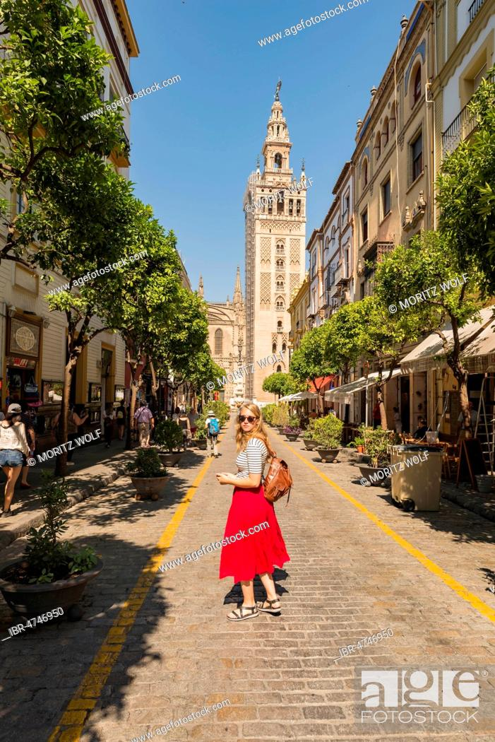 Stock Photo: Woman with red dress on street, behind La Giralda, belfry of Seville Cathedral, Catedral de Santa Maria de la Sede, Seville, Andalusia, Spain.