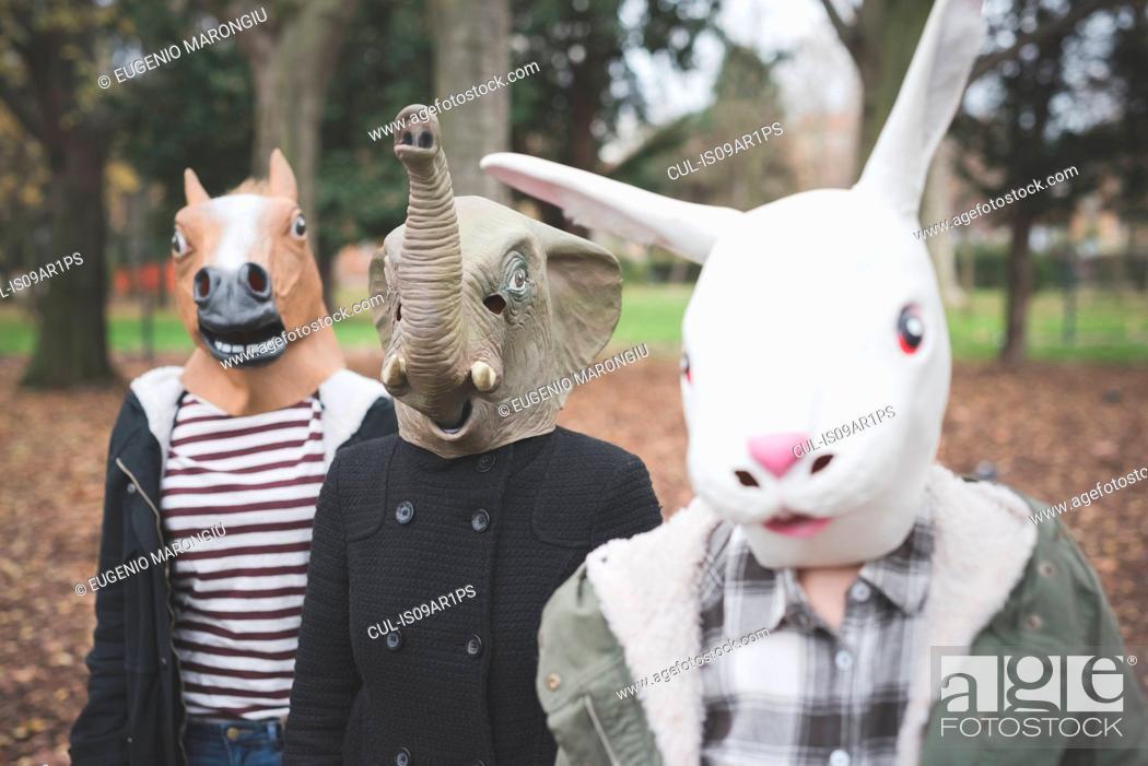 Stock Photo: Three sisters wearing animal masks posing in park.