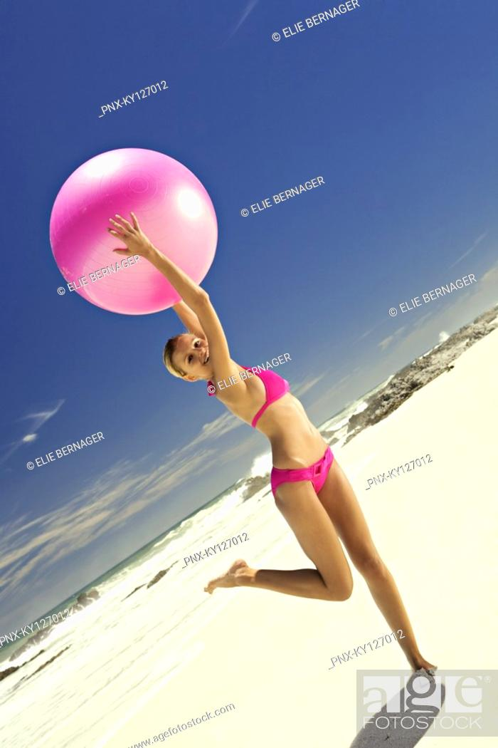 Stock Photo: Young smiling woman in pink bikini on the beach, lifting a large ball.