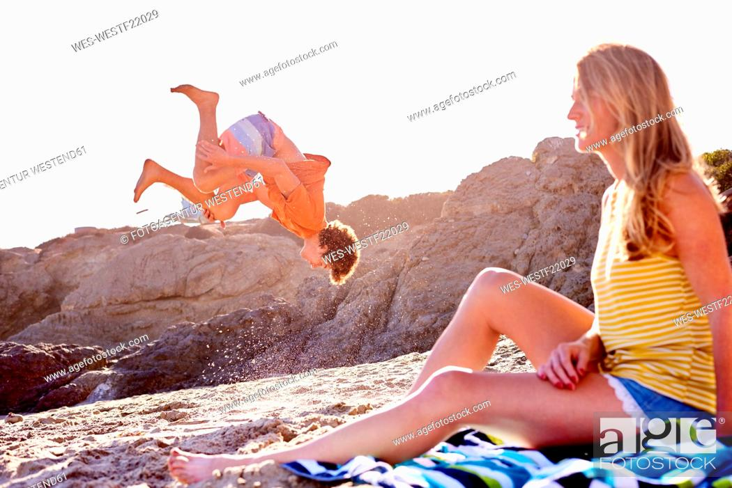 Stock Photo: Young man with woman on the beach doing a somersault.