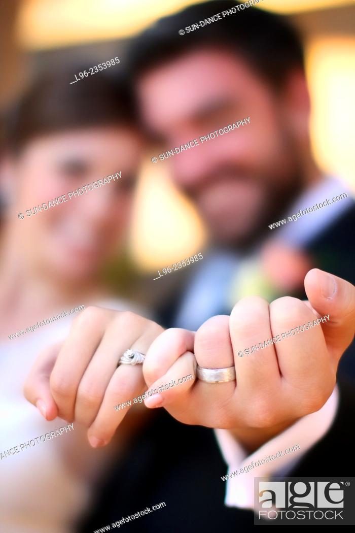 Imagen: Bride and groom smiling, showing off their wedding rings after their wedding.