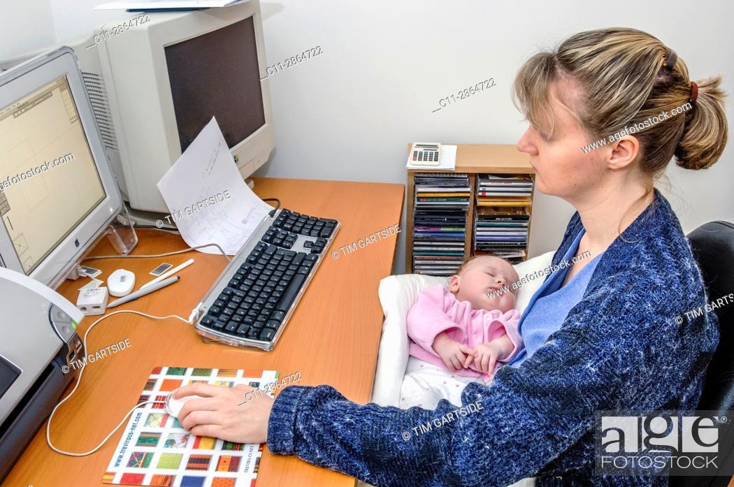 Imagen: mother working at computer holding newborn baby.