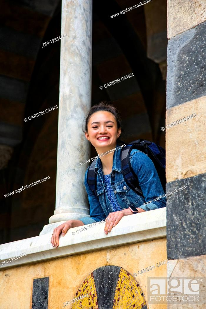 Stock Photo: A young female tourist stands on a balcony looking down at the camera; Amalfi, Italy.