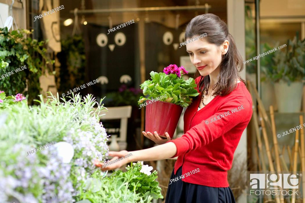 Stock Photo: Woman holding a potted plant and looking at flowers in a flower shop.