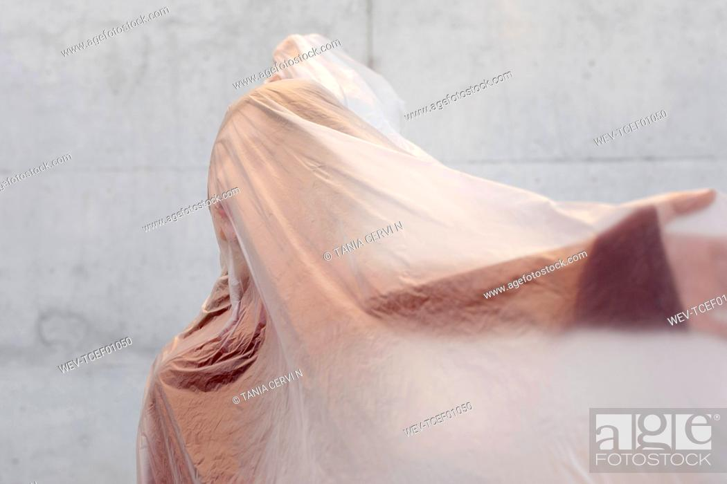 Stock Photo: Woman with arms outstretched with plastic covered on face.