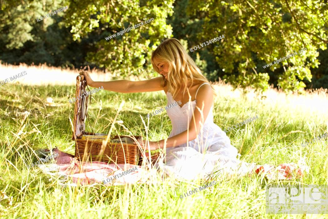 Stock Photo: A young woman opening a picnic basket.