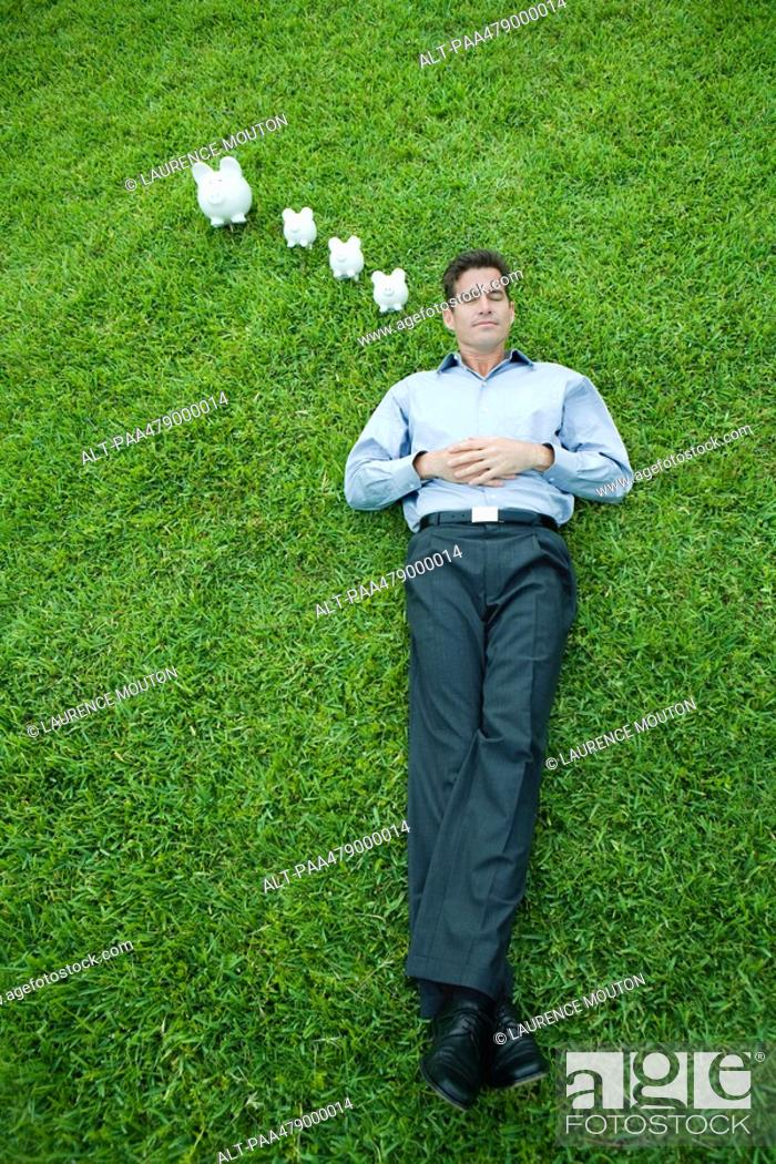 Stock Photo: Man lying on grass with eyes closed, piggy banks next to head.