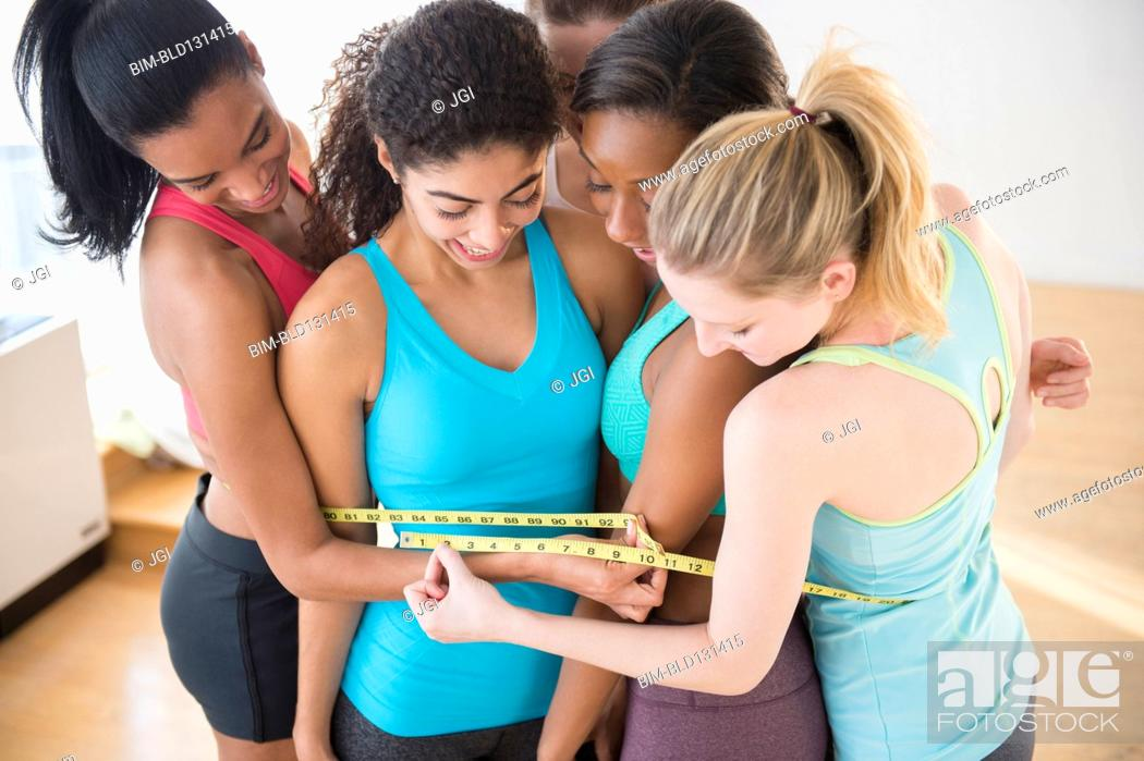 Stock Photo: Women measuring their waistlines together.