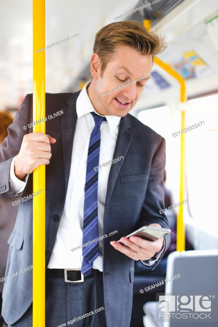 Stock Photo: Formal businessman standing on a train. He is holding the handrail with one hand and a smartphone in the other, which he is looking down at.