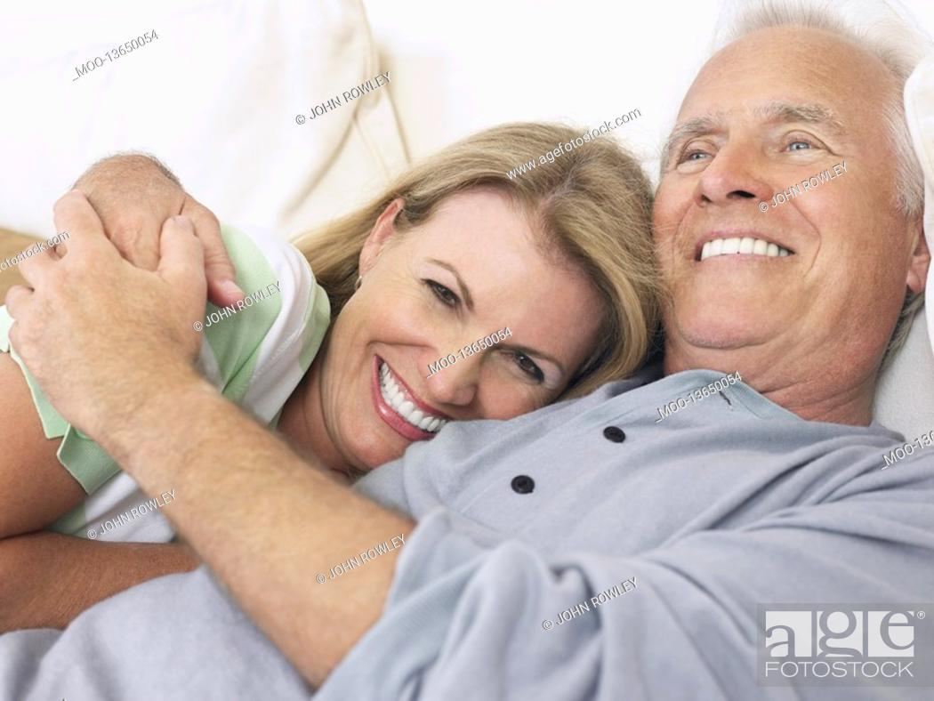 Stock Photo: Couple embracing lying in bed.