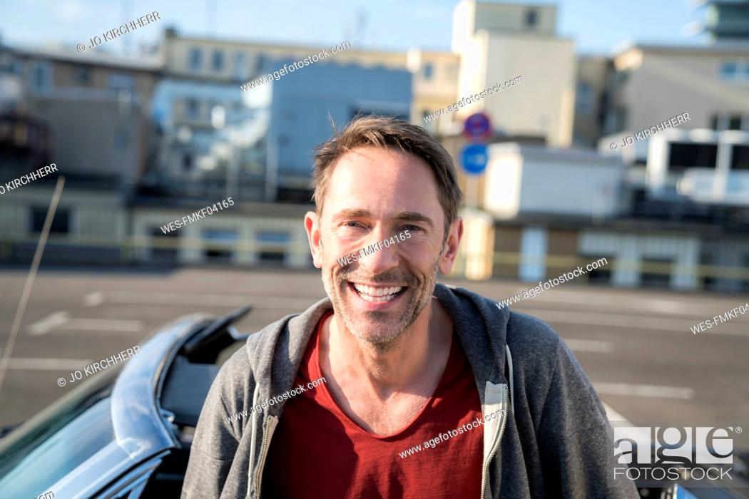 Stock Photo: Portrait of laughing mature man with stubble in front of his sports car.