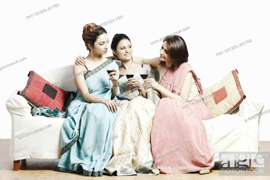 Stock Photo: Close-up of three young women sitting on a couch holding wineglasses.
