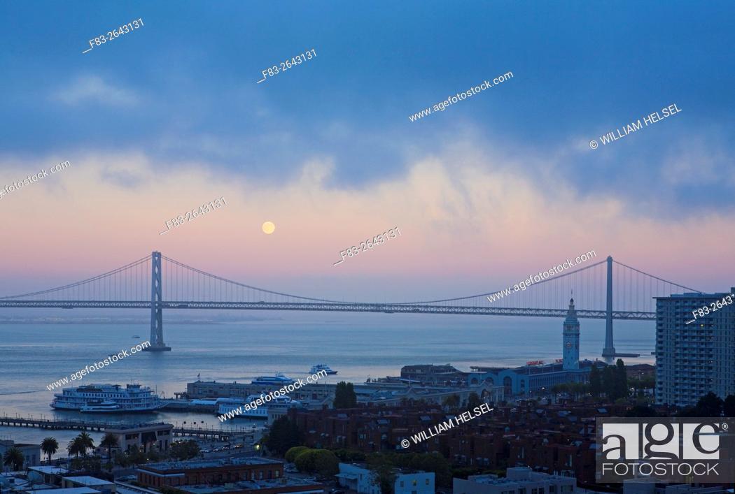 Stock Photo: Moonrise over San Francisco-Oakland Bay Bridge western span, dusk.