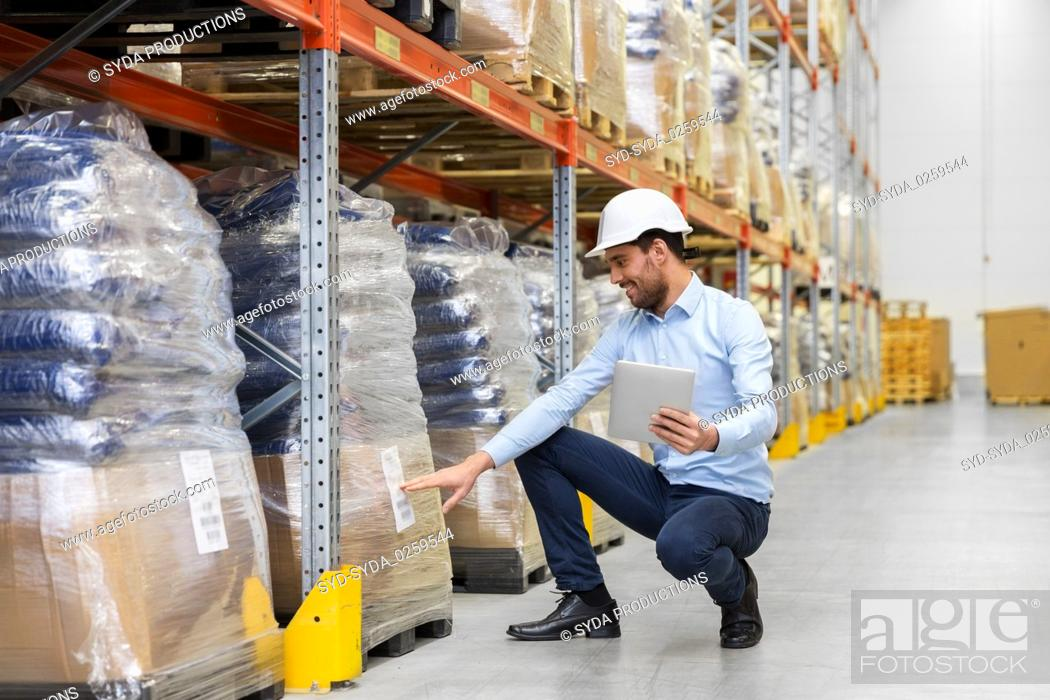 Stock Photo: happy businessman with tablet pc at warehouse.