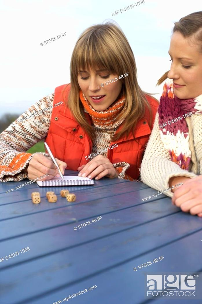 Stock Photo: Two young women gambling with dice.