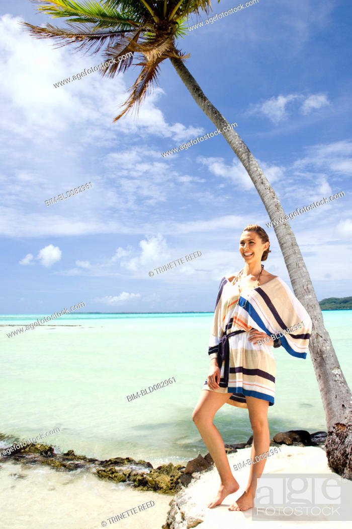 Stock Photo: Caucasian woman standing on beach near tropical ocean.