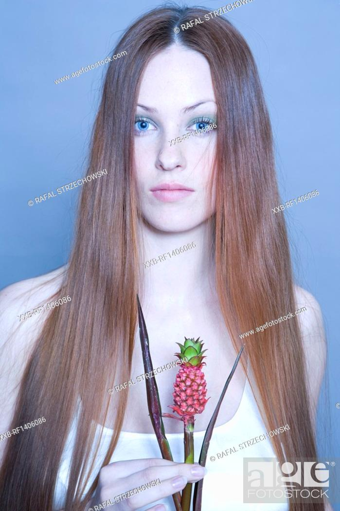 Stock Photo: young woman with pineapple plant.