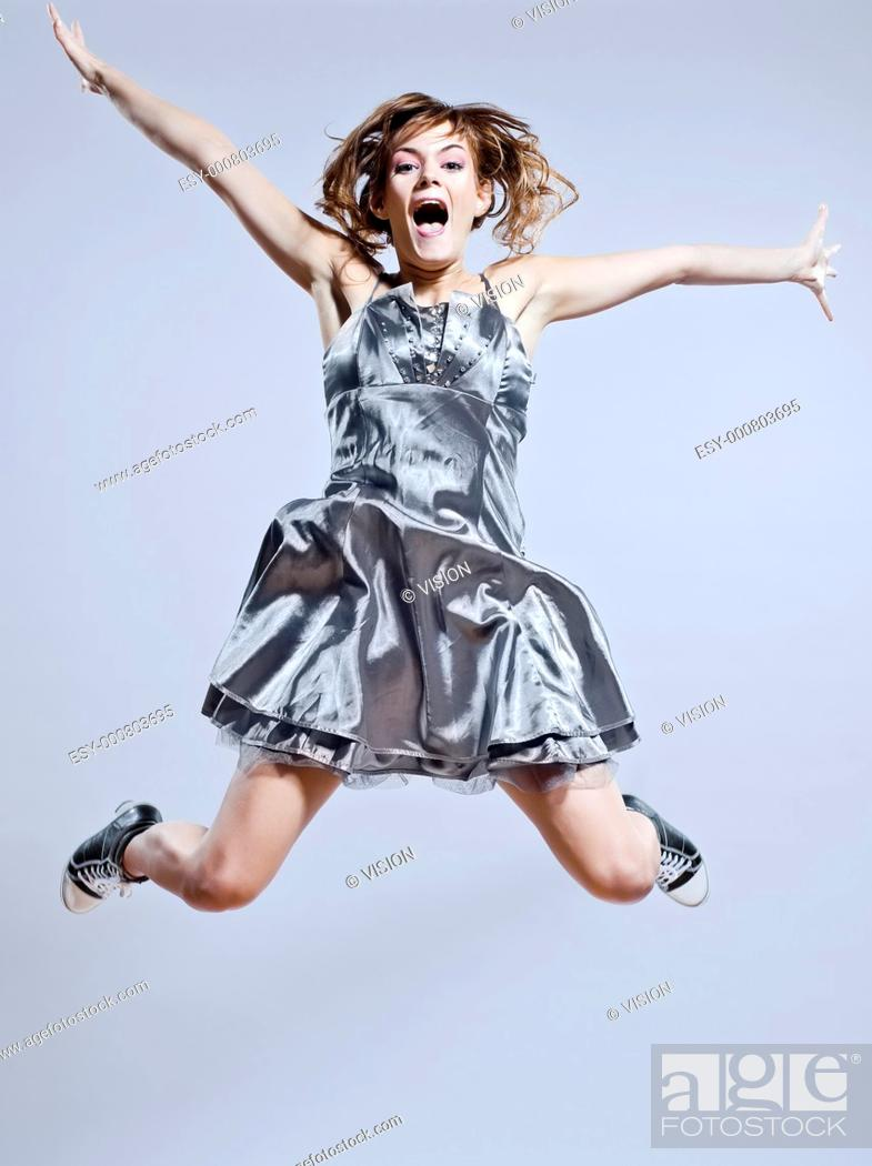 Stock Photo: beautiful young caucasian woman girl evening dress jumping screaming happy on studio isolated plain background.