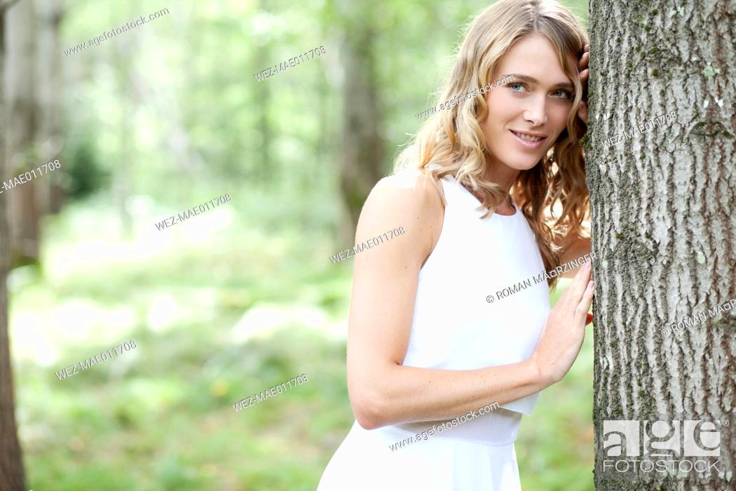 Imagen: Portrait of young woman wearing white dress in the forest.