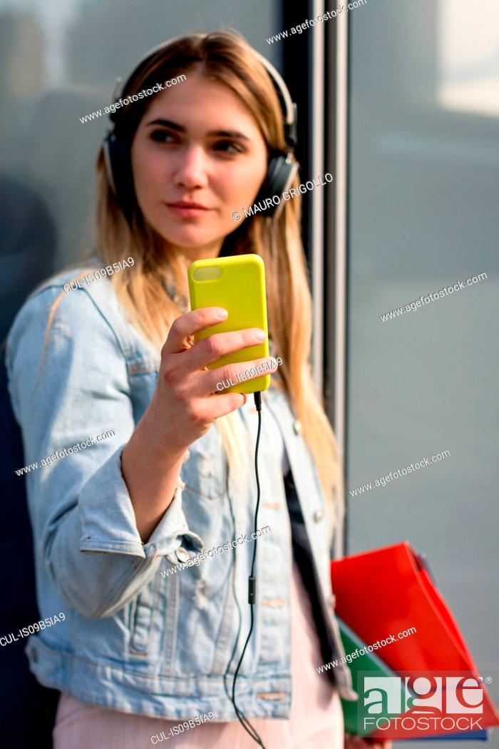 Stock Photo: Young woman, outdoors, wearing headphones, taking selfie with smartphone.
