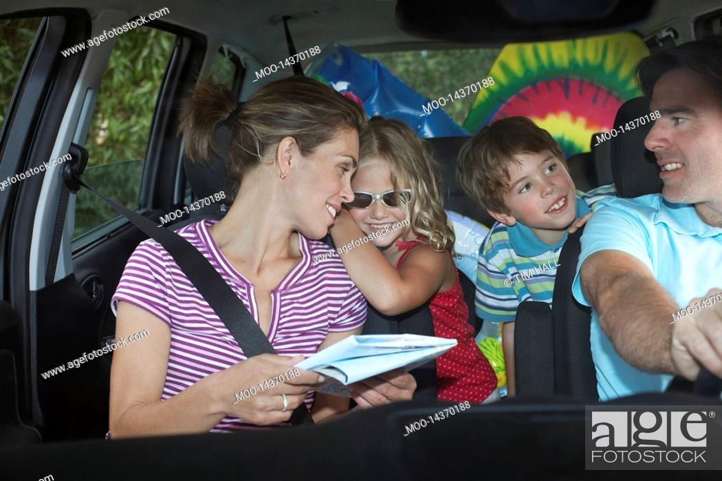 Stock Photo: Family with two children 5-6 in car interior talking.