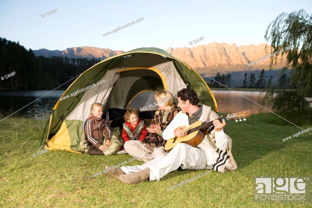 Stock Photo: Young Family camping, sitting in front of tent with father playing Guitar.