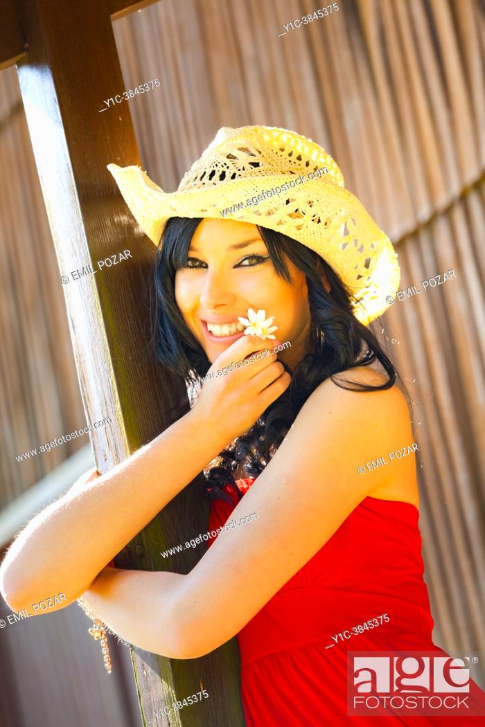 Stock Photo: Teen-girl with a stetson straw hat is holding a White flower in hand.
