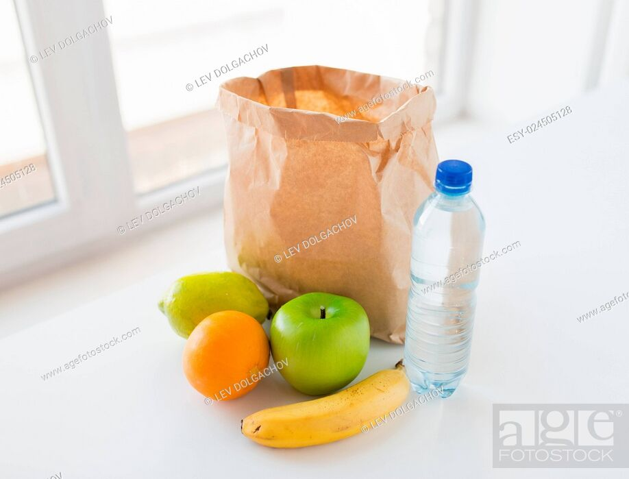 Stock Photo: cooking, diet, vegetarian food and healthy eating concept - close up of paper bag with fresh ripe juicy fruits and water bottle on kitchen table at home.