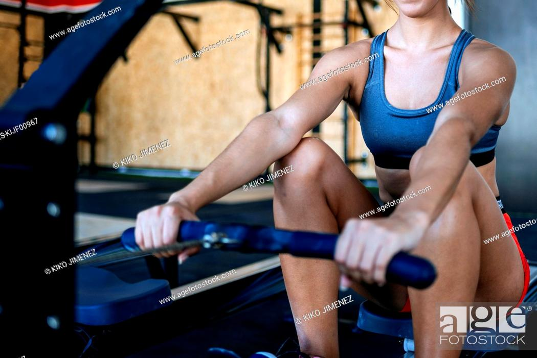 Stock Photo: Close-up of woman exercising with a rowing machine in gym.