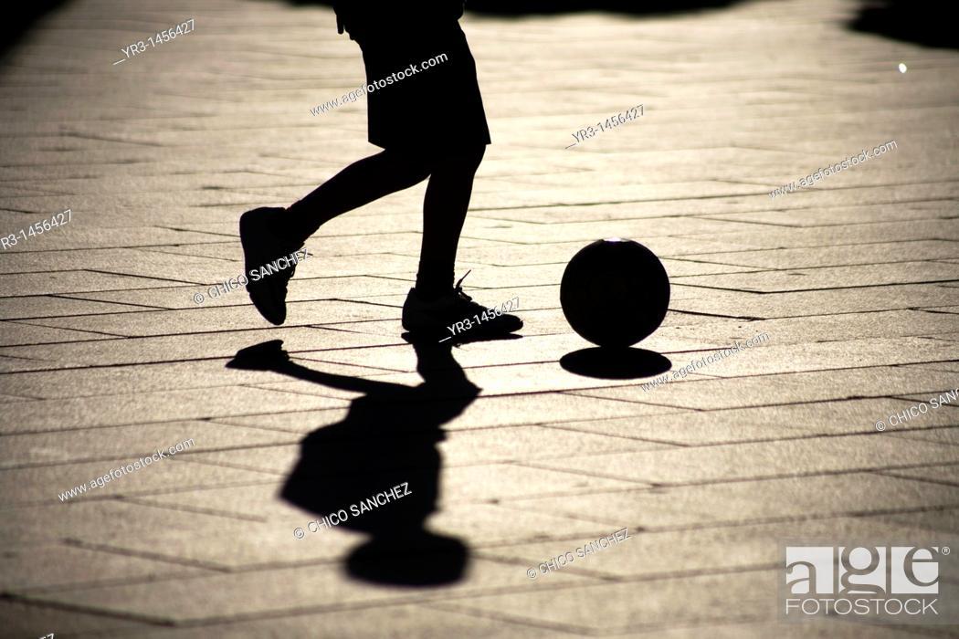 Stock Photo: A boy plays soccer in the main square of Merida, Badajoz province, Extremadura region.