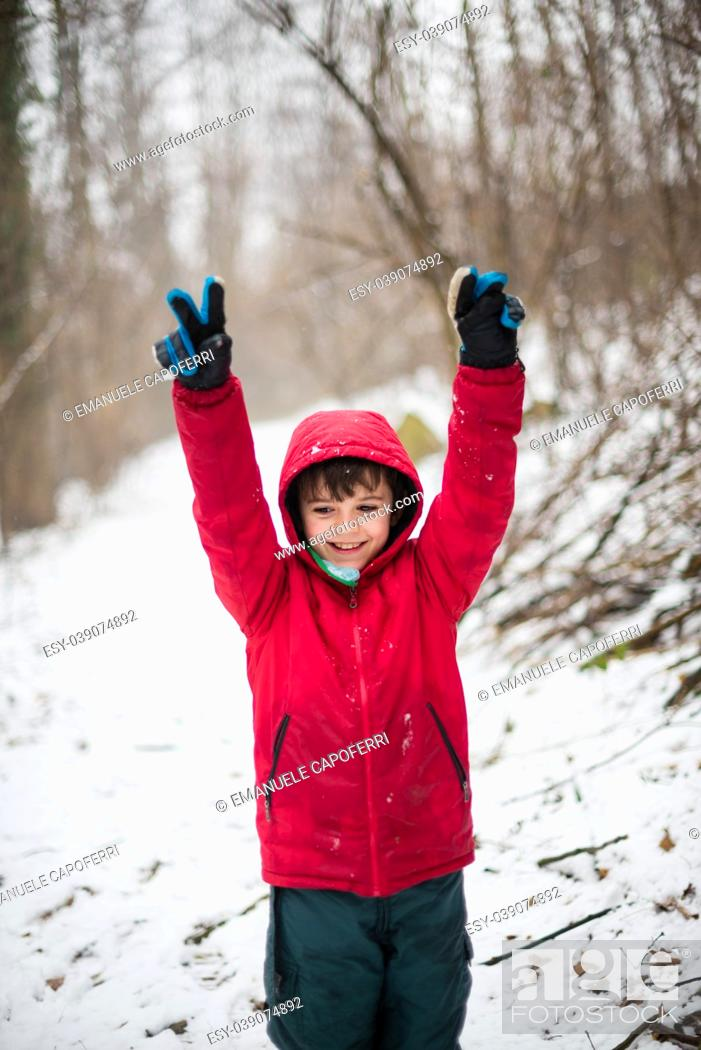 Stock Photo: portrait of smiling child and arms raised to the sky with red hat in the snowy forest.