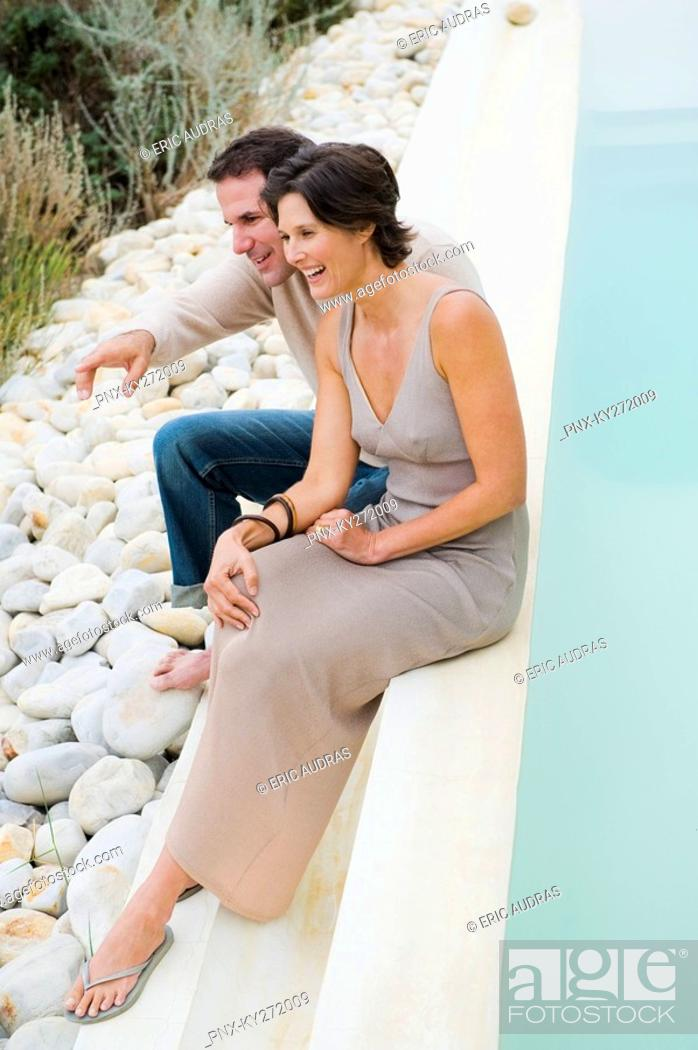 Stock Photo: Couple sitting at the poolside and admiring the view.