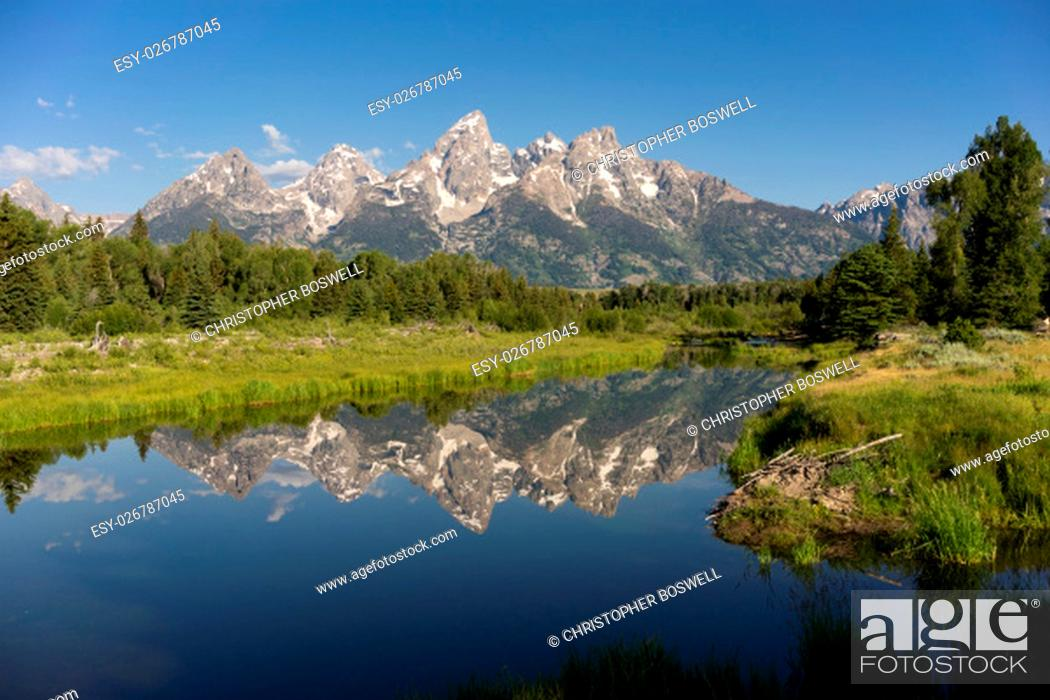 Stock Photo: The water is perfectly smooth showing high peak reflections in the Teton's.