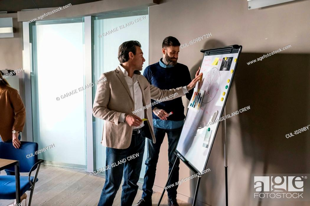 Photo de stock: Businessmen having discussion over notes on whiteboard in office.
