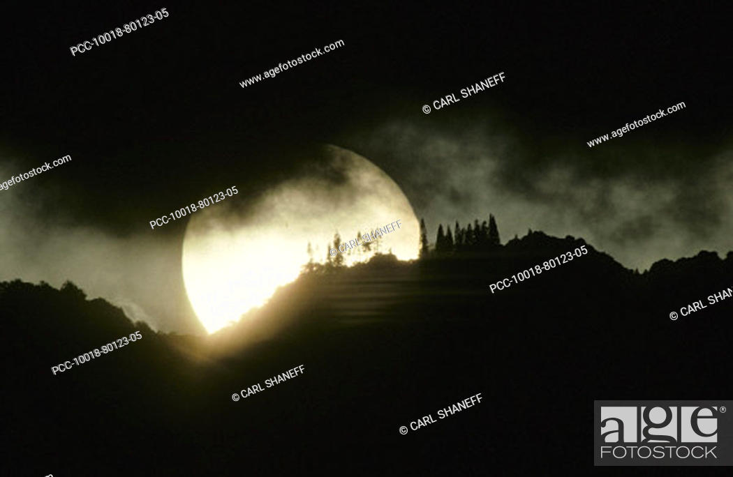 Stock Photo: Enormous sunball sinking behind mountaintop, black clouds.