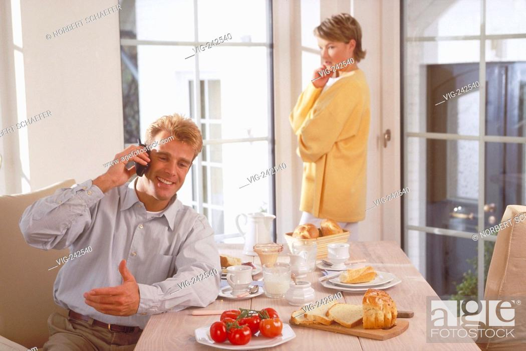 Stock Photo: indoor, half-figure, couple mid of 30, man sits at breakfast making a phone call whiles she is standing at the window watching him sceptical  - GERMANY.