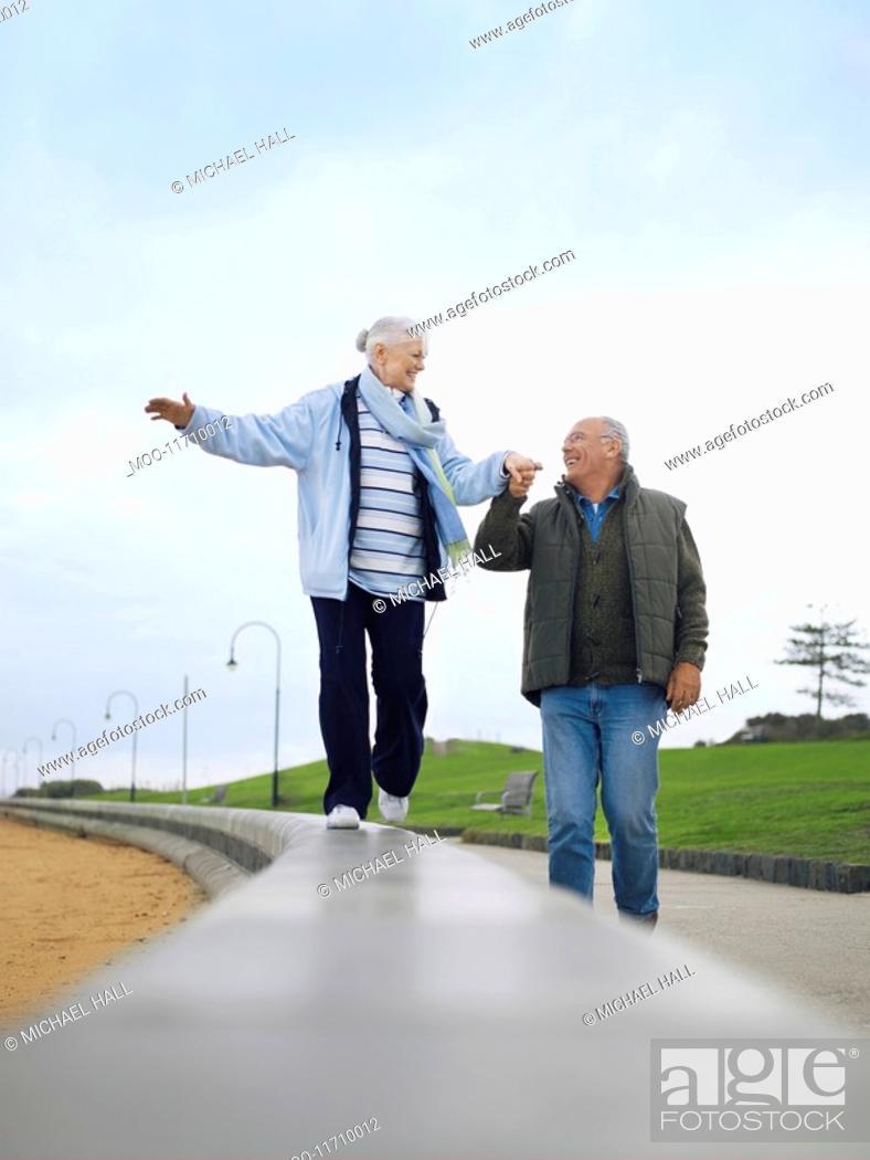 Stock Photo: Senior couple walking on wall holding hands.