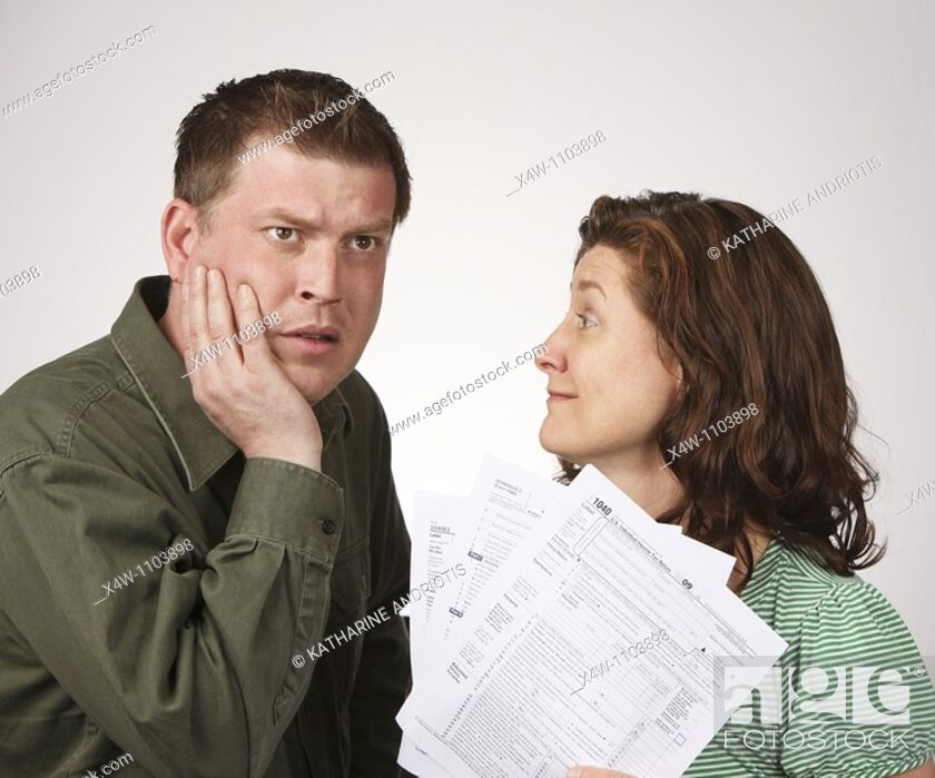 Imagen: Married couple with United States 1040 tax forms feeling anxious about their taxes.