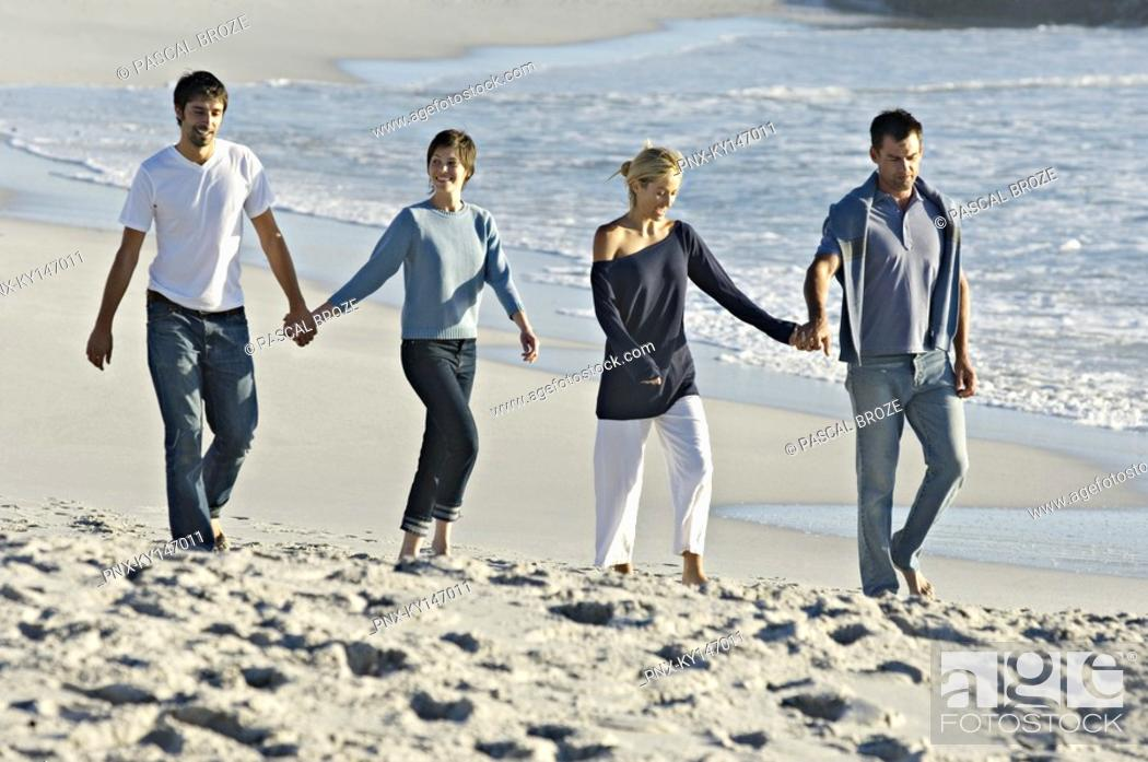 Stock Photo: 2 couples holding hands, walking on the beach.