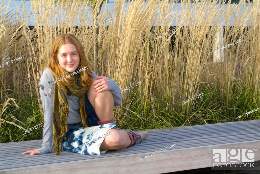 Stock Photo: young woman about 20 years of age outdoors with grasses behind her.