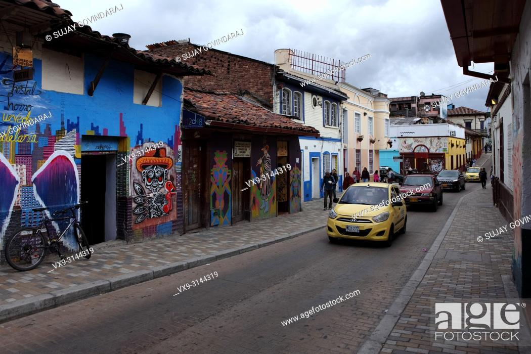 Stock Photo: Bogotá, Colombia - May 28, 2017: Traffic drives past some Street Art and Graffiti in the historic La Candelaria district in the capital city of Bogota.