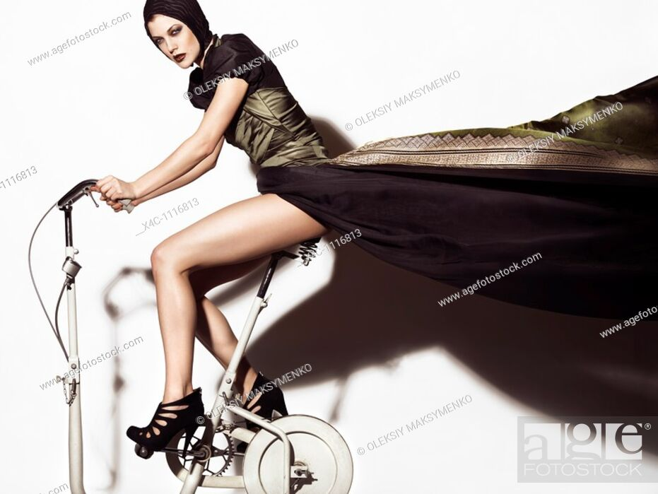 Stock Photo: Young woman in a beautiful flying in the wind long dress posing on a retro exercise bike  Edgy high fashion photo.
