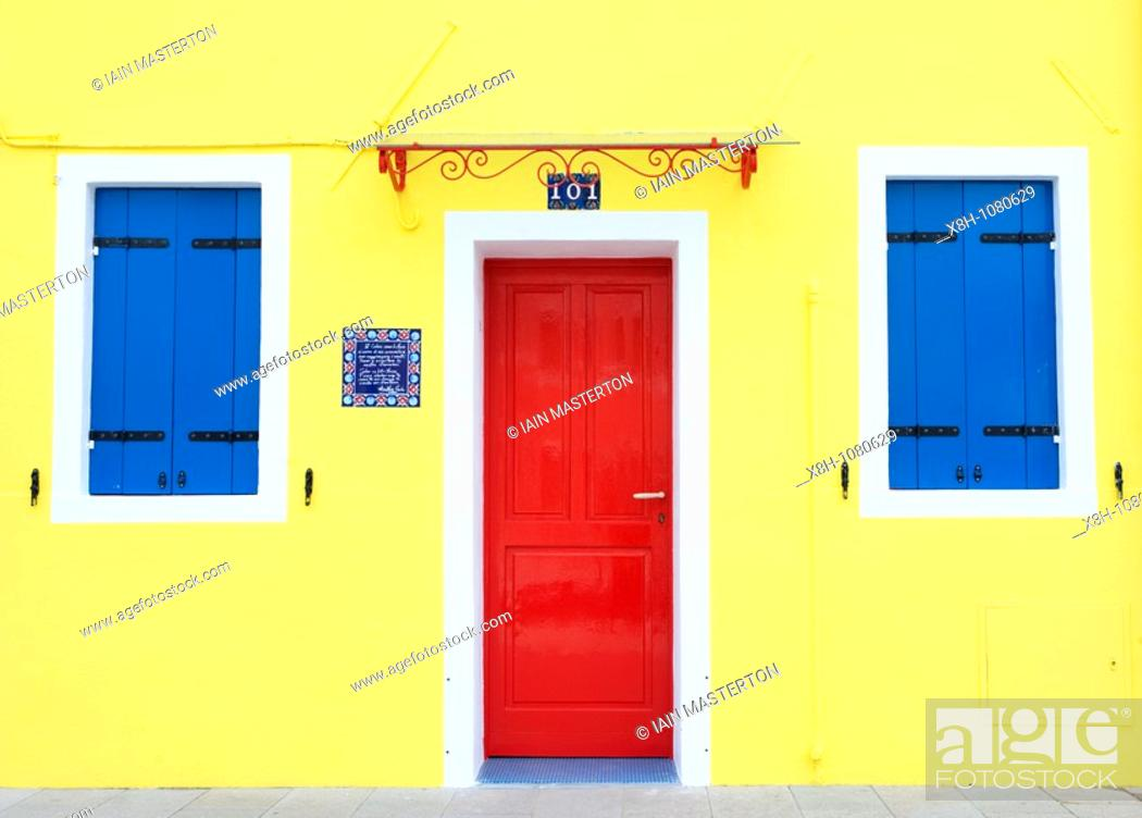 Stock Photo: Colourful yellow house in village of Burano near Venice in Italy.