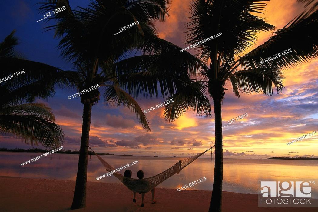 Couple Relaxing In A Hammock At Sunset Aitutaki Lagoon