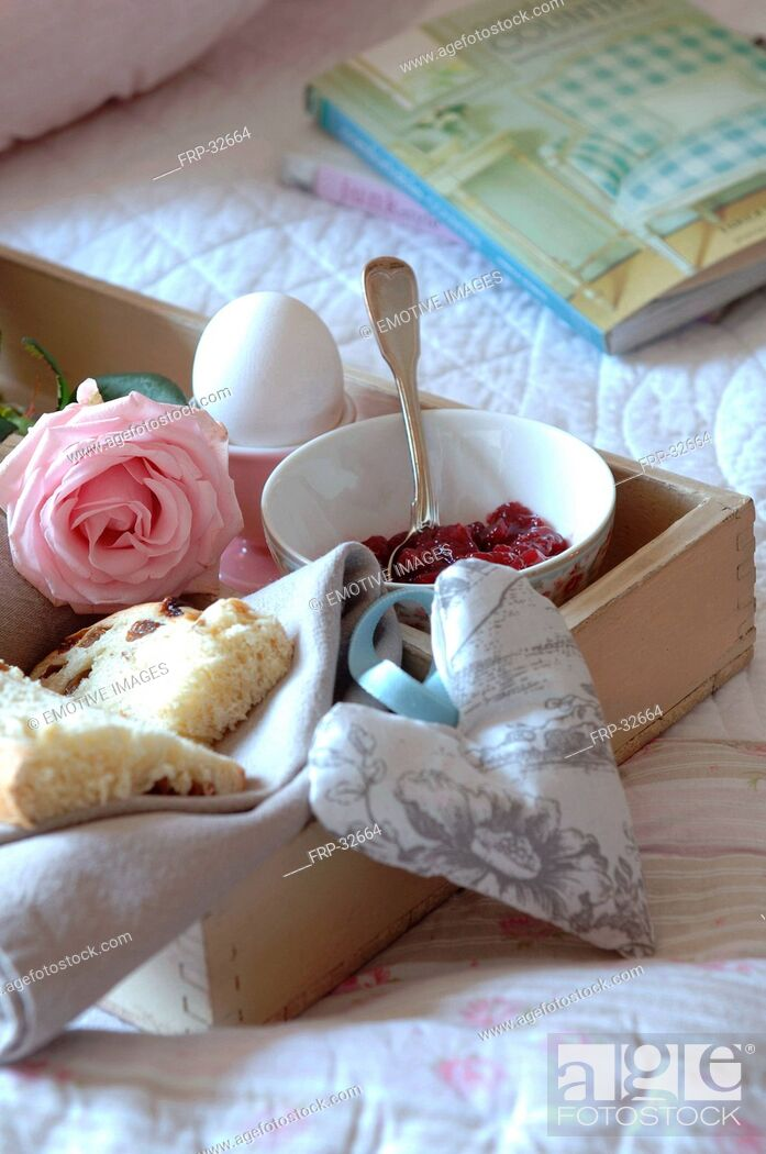 Stock Photo: Tray with jam, egg, currant bun and rose on bed.