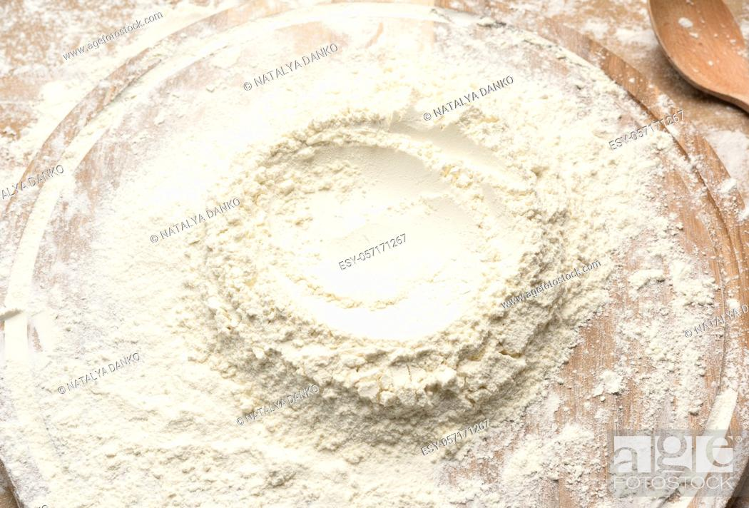 Stock Photo: white wheat flour heaped on a round wooden board, top view.